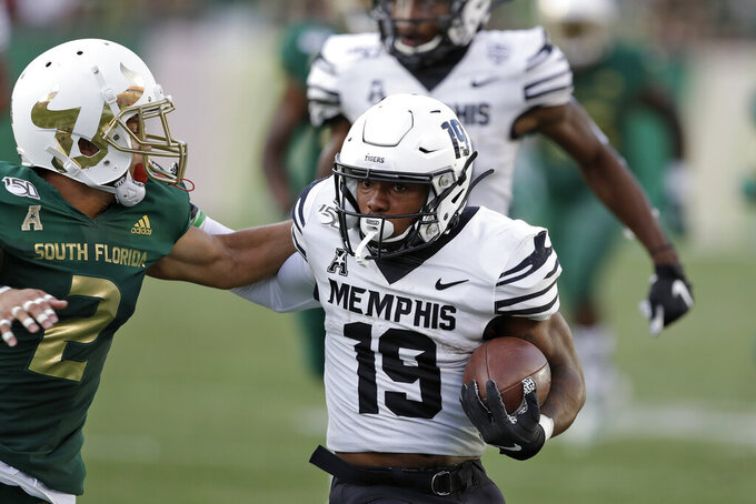 Memphis running back Kenneth Gainwell (19) pushes off South Florida defensive back Nick Roberts (2) during the first half of an NCAA college football game Saturday, Nov. 23, 2019, in Tampa, Fla. (AP Photo/Chris O'Meara)