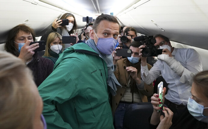FILE - In this Jan. 17, 2021, file photo, Alexei Navalny is surrounded by journalists inside the plane prior to his flight to Moscow in the Airport Berlin Brandenburg (BER) in Schoenefeld, near Berlin, Germany. The return of Navalny from Germany after he spent five months in Berlin recovering from a nerve agent poisoning was marked by chaos and popular outrage, and it ended, almost predictably with his arrest. The Jan. 17 flight carried him and his wife, along with a group of journalists documenting the journey. (AP Photo/Mstyslav Chernov, File)