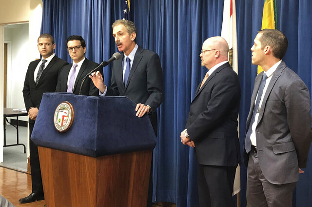FILE - In this Jan. 4, 2019, file photo, Los Angeles City Attorney Mike Feuer, at podium, speaks at a news conference in Los Angeles. The operator of The Weather Channel mobile app has agreed to change how it informs users about its location-tracking practices and sale of personal data as part of a settlement with the Los Angeles city attorney's office, officials said Wednesday, Aug. 19, 2020. Feuer alleged in a 2019 lawsuit in Los Angeles County Superior Court that app users were misled when they agreed to share their location information in exchange for personalized forecasts and alerts. (AP Photo/Brian Melley, File)