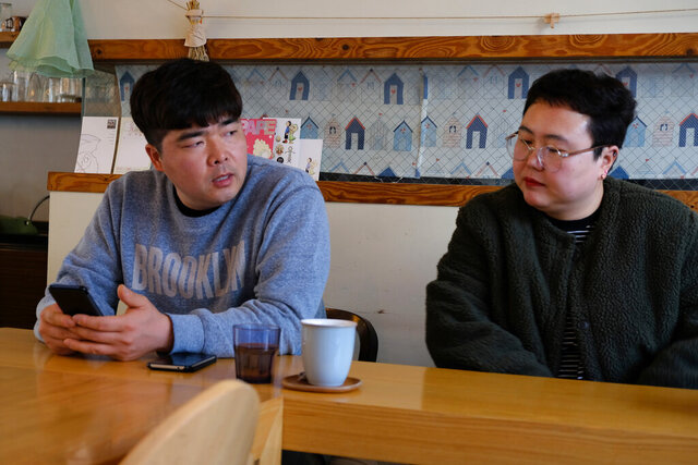 In this Wednesday, Feb. 19, 2020, photo, props manager Joo Dong-man, left, speaks as costume manager Yang Hee-hwa listens during an interview at a cafe in Ilsan, South Korea. South Korea's latest hit drama