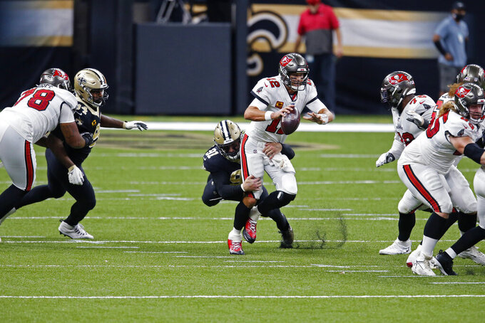Tampa Bay Buccaneers quarterback Tom Brady (12) scrambles under pressure from New Orleans Saints defensive end Trey Hendrickson (91) in the first half of an NFL football game in New Orleans, Sunday, Sept. 13, 2020. (AP Photo/Butch Dill)