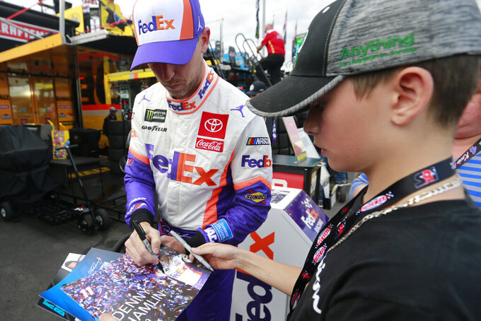 Denny Hamlin, left, signs an autograph for a fan after qualifying for the NASCAR Cup Series race at Martinsville Speedway in Martinsville, Va., Saturday, Oct. 26, 2019. Hamlin won the pole. (AP Photo/Steve Helber)