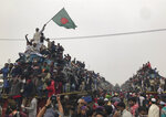 In this Jan. 12, 2020, photo, a man waves Bangladeshi flag as Muslims board over-crowded trains as they prepare to return to their homes after attending a three-day Islamic congregation in Dhaka, Bangladesh. The Biswa Ijtema, or the World Congregation of Muslims, is considered as one of the largest gatherings of the Muslim devotees. (AP Photo/Al-emrun Garjon, File)