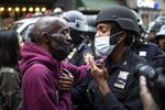 A protester and a police officer shake hands in the middle of a standoff during a solidarity rally calling for justice over the death of George Floyd Tuesday, June 2, 2020, in New York. Floyd died after being restrained by Minneapolis police officers on May 25. (AP Photo/Wong Maye-E)