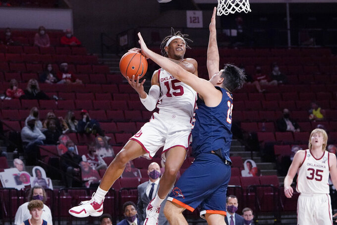 Oklahoma guard Alondes Williams (15) goes up for a shot in front of UTSA forward Adrian Rodriguez (25) during the first half of an NCAA college basketball game Thursday, Dec. 3, 2020, in Norman, Okla. (AP Photo/Sue Ogrocki)