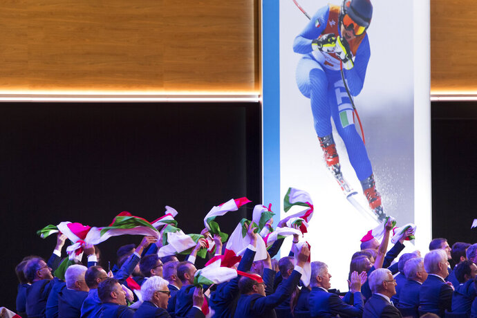 Italy members of delegation cheer with Italian flags during the final presentation of the Milan-Cortina candidate cities the first day of the 134th Session of the International Olympic Committee (IOC), at the SwissTech Convention Centre, in Lausanne, Switzerland, Monday, June 24, 2019. The host city of the 2026 Olympic Winter Games will be decided during the134th IOC Session. Stockholm-Are in Sweden and Milan-Cortina in Italy are the two candidate cities for the Olympic Winter Games 2026. (Laurent Gillieron/Keystone via AP)
