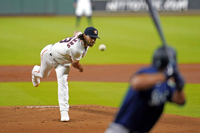 Houston Astros starting pitcher Lance McCullers Jr., left, throws to Seattle Mariners' Evan White during the first inning of a baseball game Saturday, July 25, 2020, in Houston. (AP Photo/David J. Phillip)