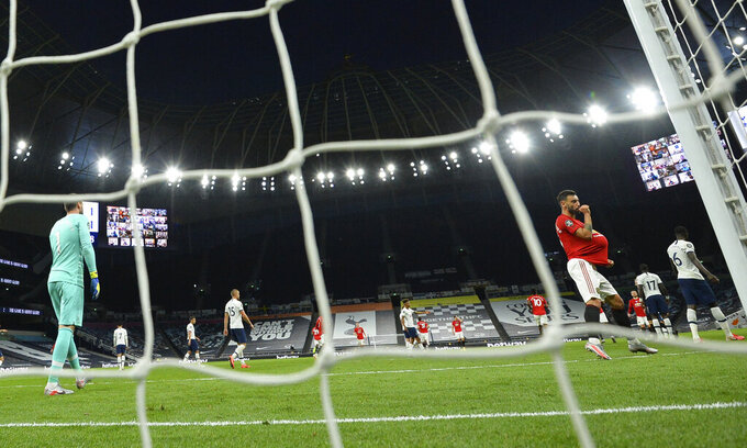 Manchester United's Bruno Fernandes, right, celebrates after scoring their first goal from the penalty spot during the English Premier League soccer match between Tottenham Hotspur and Manchester United at Tottenham Hotspur Stadium in London, England, Friday, June 19, 2020. (AP Photo/Glyn Kirk, Pool)
