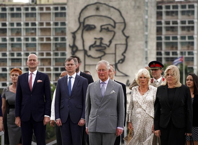 Backdropped by an image of Che Guevara, Britain's Prince Charles, the Prince of Wales, center, and Camilla, Duchess of Cornwall, center right, attend a wreath-laying ceremony at the Jose Marti Monument during their official visit in Havana, Cuba, Sunday, March 24, 2019. (AP Photo/Ramon Espinosa)