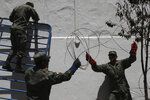 Solsiers removes ribbons of razor wire from the perimeters of Carondelet Palace, the seat of government, in Quito Ecuador, Monday, Oct. 14, 2019. Cleanup  of the capital began hours after President Lenín Moreno and indigenous leaders struck a deal late Sunday to cancel a disputed austerity package and end nearly two weeks of protests that paralyzed the Ecuadorian economy and left seven dead. (AP Photo/Dolores Ochoa)