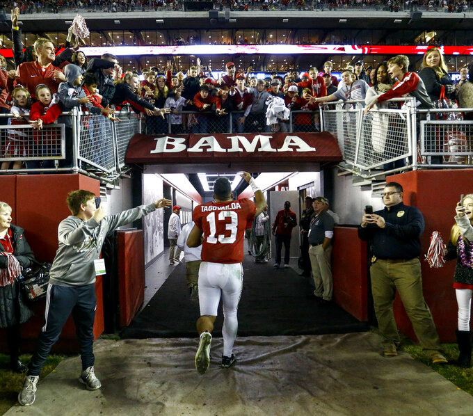 Alabama quarterback Tua Tagovailoa (13) waves to fans as he runs off the field after an NCAA college football game against Auburn, Saturday, Nov. 24, 2018, in Tuscaloosa, Ala. (AP Photo/Butch Dill)