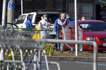 Police forensic staff stand outside a supermarket in Auckland, New Zealand, Saturday, Sept. 4, 2021. New Zealand authorities say they shot and killed a violent extremist, Friday Sept. 3, after he entered a supermarket and stabbed and injured six shoppers. Prime Minister Jacinda Ardern described Friday's incident as a terror attack. (AP Photo/Brett Phibbs)