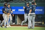 Seattle Mariners' Mitch Haniger, second from right, is congratulated by Kyle Seager (15), J.P. Crawford, left, and Jake Bauers (5) after hitting a three run home run that scored Bauers and Crawford during the second inning of a baseball game against the Texas Rangers Thursday, Aug. 19, 2021, in Arlington, Texas. (AP Photo/Jeffrey McWhorter)