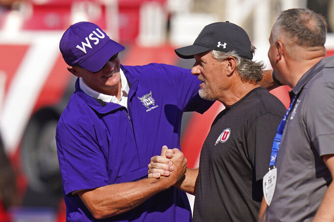 Utah coach Kyle Whittingham, right, and Weber State coach Jay Hill hake hands before an NCAA college football game Thursday, Sept. 2, 2021, in Salt Lake City. (AP Photo/Rick Bowmer)