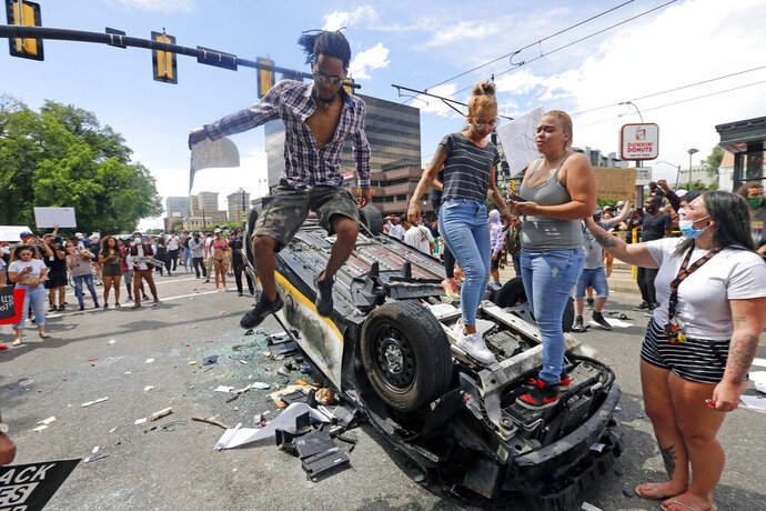 FILE - in this Saturday, May 30, 2020 file photo, protesters climb on a flipped over police vehicle, in Salt Lake City. Protests in Salt Lake City that drew several thousand people are a setback for contact tracers already struggling to contain the spread of the coronavirus, said Tair Kiphibane, infectious disease bureau manager for the Salt Lake County Health Department. (AP Photo/Rick Bowmer, File)