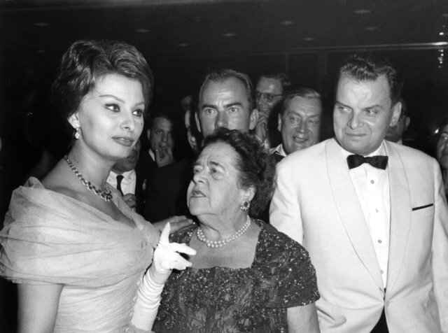 File--- File picture taken on July 4, 1959 shows Italian actress Sophia Loren, American journalist Elsa Maxwell and festival director Dr. Alfred Bauer, right, talk at the festival in the Palais am Funkturm in Berlin. (Konrad Giehr/dpa via AP, file)