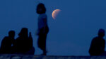 Residents watch the lunar eclipse at Sanur beach in Bali, Indonesia on Wednesday, May 26, 2021. The total lunar eclipse, also known as a super blood moon, is the first in two years with the reddish-orange color the result of all the sunrises and sunsets in Earth's atmosphere projected onto the surface of the eclipsed moon. (AP Photo/Firdia Lisnawati)