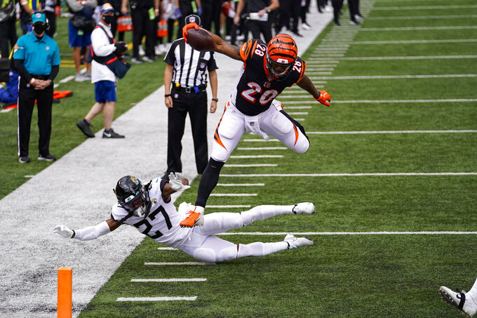 Cincinnati Bengals running back Joe Mixon (28) leaps over Jacksonville Jaguars cornerback Chris Claybrooks (27) for a touchdown in the first half of an NFL football game in Cincinnati, Sunday, Oct. 4, 2020. (AP Photo/Bryan Woolston)