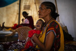 FILE - In this Tuesday May 11, 2021 file photo, Roman Kidanemariam, 35, holds her malnourished daughter, Merkab Ataklti, 22 months old, in the treatment tent of a medical clinic in the town of Abi Adi, in the Tigray region of northern Ethiopia. Samantha Power, the U.S. official who wrote a Pulitzer Prize-winning book on genocide is visiting Ethiopia next week to press the government to lift what the U.S. calls a blockade on humanitarian aid to the conflict-hit Tigray region, where hundreds of thousands of people now face deadly famine. (AP Photo/Ben Curtis, File)