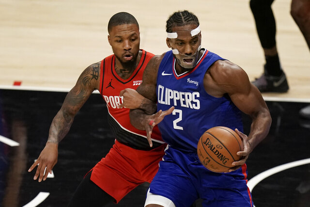 Portland Trail Blazers' Damian Lillard, left, grabs the arm of Los Angeles Clippers' Kawhi Leonard during the first half of an NBA basketball game Wednesday, Dec. 30, 2020, in Los Angeles. (AP Photo/Jae C. Hong)