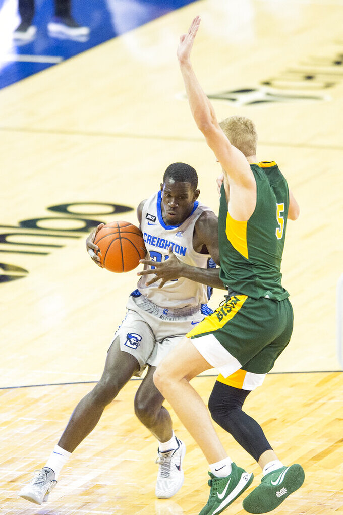 Creighton's Damien Jefferson, left, drives to the hoop against North Dakota State's Sam Griesel, right, during the second half of an NCAA college basketball game in Omaha, Neb., Sunday, Nov. 29, 2020. (AP Photo/Kayla Wolf)