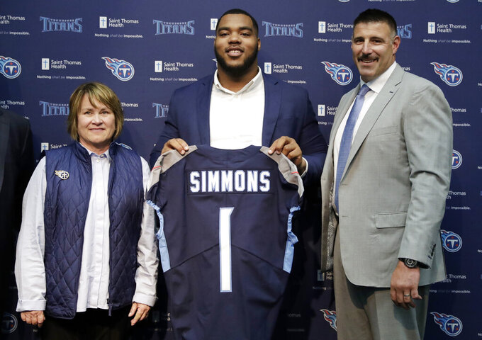 Mississippi State defensive tackle Jeffery Simmons, center, poses with Tennessee Titans owner Amy Adams Strunk, left, and head coach Mike Vrabel, right, during an NFL football news conference Friday, April 26, 2019, in Nashville, Tenn. Simmons was selected in the first round by the Titans. (AP Photo/Mark Humphrey)