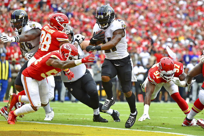 Baltimore Ravens running back Mark Ingram II (21) runs the ball in for a touchdown between Kansas City Chiefs linebacker Damien Wilson, left, and defensive end Alex Okafor (97) during the first half of an NFL football game in Kansas City, Mo., Sunday, Sept. 22, 2019. (AP Photo/Ed Zurga)