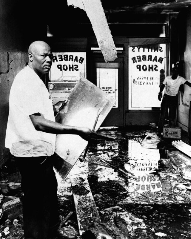 FILE - In this Aug. 17, 1965 file photo, A.Z. Smith, a victim of the Los Angeles riots, checks the damage to his barber shop in the Watts area of Los Angeles. Business establishments owned by whites were the usual targets of looters and arsonists. Smith was one of the few blacks caught up in the turmoil. (AP Photo)