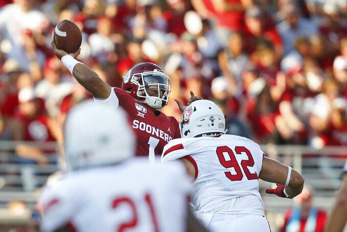 Oklahoma quarterback Jalen Hurts (1) throws under pressure from South Dakota defensive lineman Kameron Cline in the first quarter of an NCAA college football game Saturday, Sept. 7, 2019, in Norman, Okla. (AP Photo/Sue Ogrocki)