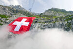File---Picture taken July 31, 2009 shows the world largest Swiss flag hanging at the rock face of the mountain Saentis in Schwaegalp, Switzerland, The flag measures 120 meters square and is believed to be the world second largest flag. Tomorrow Aug. 1, Switzerland is celebrating the national holiday. (Ennio Leanza/Keystone via AP)