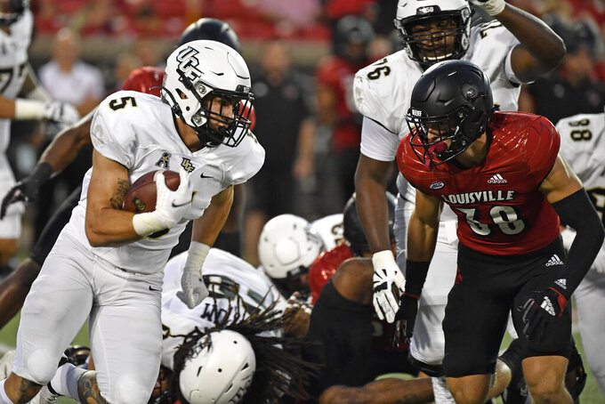 Central Florida running back Isaiah Bowser (5) attempts to get past an oncoming rush by Louisville safety Shavarick Williams (30) during the first half of an NCAA college football game in Louisville, Ky., Friday, Sept. 17, 2021. (AP Photo/Timothy D. Easley)