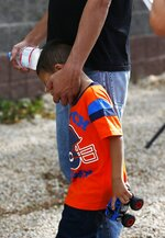 Jose and his 3-year-old son Jose Jr., from Honduras, share a moment after they were reunited Tuesday, July 10, 2018, in Phoenix. Lugging little backpacks, smiling immigrant children were scooped up into their parents' arms Tuesday as the Trump administration scrambled to meet a court-ordered deadline to reunite dozens of youngsters forcibly separated from their families at the border. (AP Photo/Ross D. Franklin)