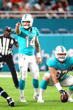 Miami Dolphins quarterback Ryan Fitzpatrick (14) alerts the offensive line to a defensive scheme in an NFL preseason game against the Jacksonville Jaguars, Thursday, Aug. 22, 2019, in Miami Gardens, Fla. (Margaret Bowles via AP)