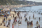 People relax on the beach at Bournemouth, Southern England, Friday Aug. 7, 2020.  The UK could see record-breaking temperatures with forecasters predicting Friday could be the hottest day of the year. (Andrew Matthews/PA via AP)