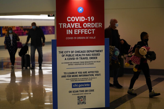 FILE - In this Nov. 24, 2020 file photo, air travelers arriving at Midway Airport in Chicago are reminded of the city's COVID-19 travel orders. More than 1 million people have passed through U.S. airport security checkpoints in each of the past two days in a sign that public health pleas to avoid holiday travel are being ignored, despite an alarming surge in COVID-19 cases. (AP Photo/Charles Rex Arbogast, File)