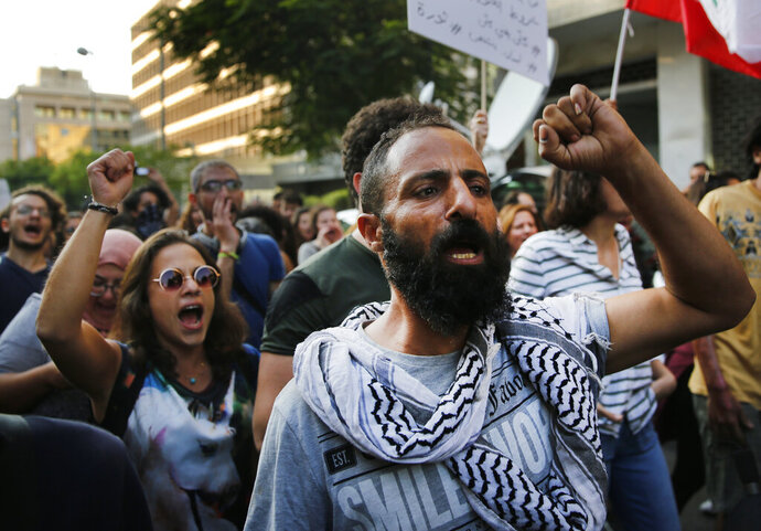 Anti-government protesters shout slogans, as they march during a protest against the central bank and the Lebanese government, in Beirut, Lebanon, Thursday, Oct. 31, 2019. Lebanese security forces were still struggling to open some roads Thursday as protesters continued their civil disobedience campaign in support of nationwide anti-government demonstrations. (AP Photo/Hussein Malla)