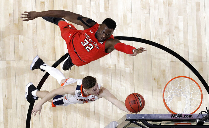 Virginia's Kyle Guy (5) takes a shot against Texas Tech's Norense Odiase (32) during the second half in the championship of the Final Four NCAA college basketball tournament, Monday, April 8, 2019, in Minneapolis. (AP Photo/David J. Phillip)