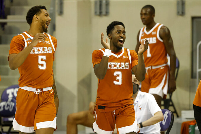 Texas forward Royce Hamm Jr. (5) and guard Courtney Ramey (3) celebrate their victory over TCU in an NCAA college basketball game in Fort Worth, Texas, Sunday, March 7, 2021. (AP Photo/Michael Ainsworth)