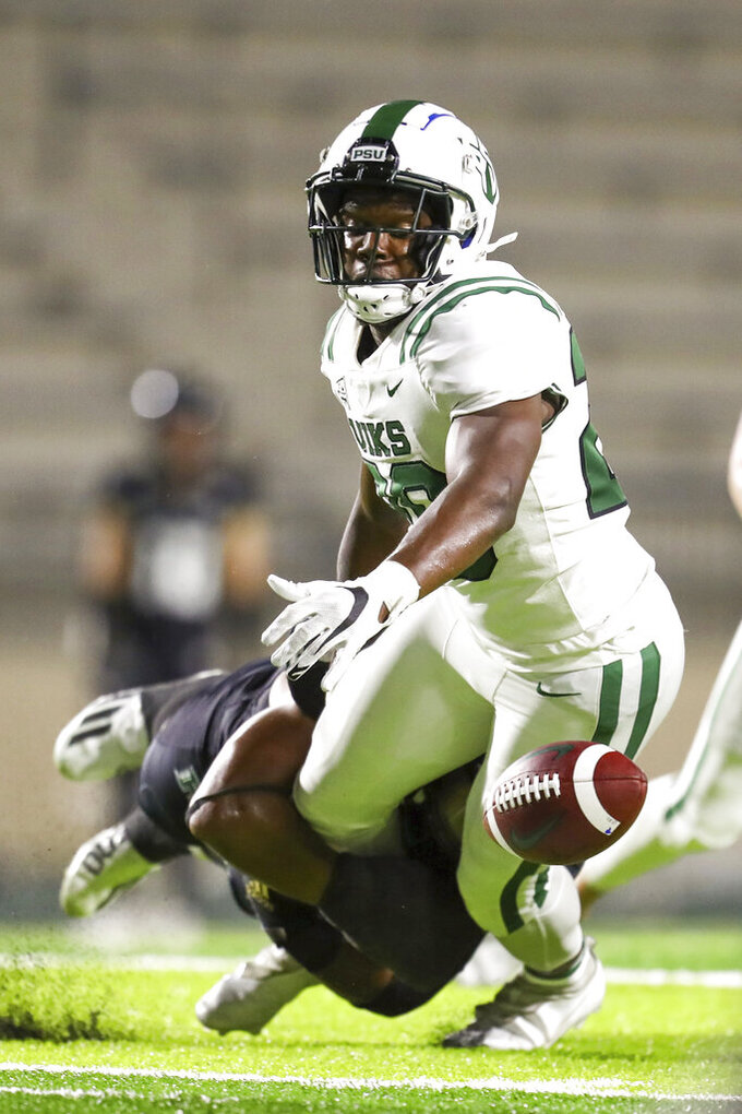 Hawaii linebacker Darius Muasau, left, forces Portland State running back Jalynnee McGee (29) to fumble to the ball during the second half of an NCAA college football game, Saturday, Sept. 4, 2021, in Honolulu. (AP Photo/Darryl Oumi)