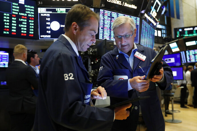 FILE - In this Aug. 16, 2019, file photo traders Dudley Devine, left, and Christopher Fuchs work on the floor of the New York Stock Exchange. The U.S. stock market opens at 9:30 a.m. EDT on Thursday, Aug. 22. (AP Photo/Richard Drew, File)