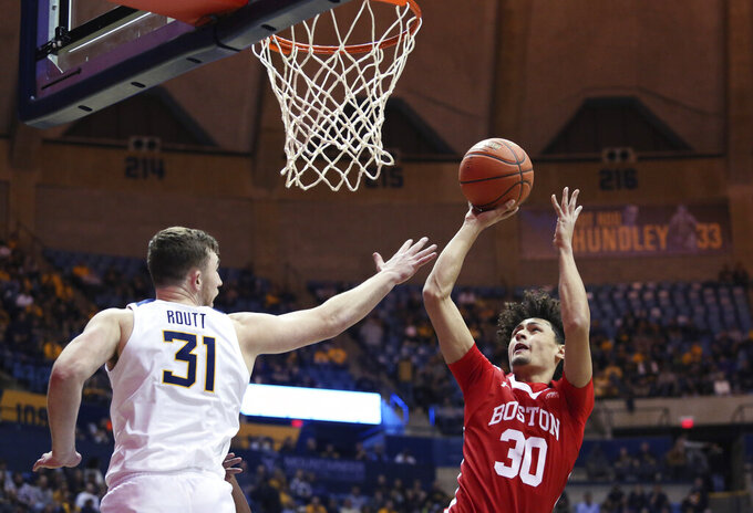 West Virginia forward Logan Routt (31) defends against Boston University guard Javante McCoy (30) during the first half of an NCAA college basketball game Friday, Nov. 22, 2019, in Morgantown, W.Va. (AP Photo/Kathleen Batten)