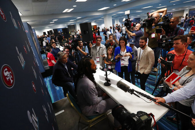 San Francisco 49ers cornerback Richard Sherman, center, answers questions during a media availability for the NFL Super Bowl 54 football game, on Tuesday, Jan. 28, 2020, in Miami. (AP Photo/Wilfredo Lee)