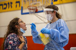 A medical worker tests a woman for the coronavirus at a basketball court turned into a coronavirus testing center, in Binyamina, Israel, Tuesday, June 29, 2021. Israel's prime minister is urging the country's youth to get vaccinated as coronavirus case numbers have crept up in recent days due to a localized outbreak of the Delta variant. (AP Photo/Ariel Schalit)