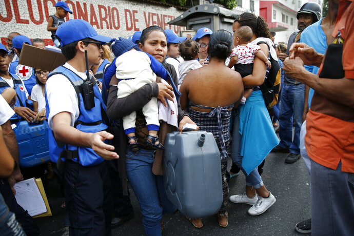 A woman with a child carries an empty container and water purification pills that came in the first aid shipment from the International Red Cross in Caracas, Venezuela, Tuesday, April 16, 2019. The first shipment of humanitarian aid from the Red Cross arrived in Venezuela on Tuesday, delivering medicine and supplies for needy patients in a country whose president has long denied the existence of a humanitarian crisis. (AP Photo/Ariana Cubillos)