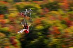 FILE - In this Sept. 23, 2017, file photo, Katie McWalter of Southborough, Mass., sails by fall foliage while riding the ZipRider at Wildcat Mountain in Pinkham Notch, N.H. The coronavirus pandemic in 2020 not only upended the tourism industry, but how states, cities and attractions market themselves as summer travel destinations. (AP Photo/Robert F. Bukaty, File)