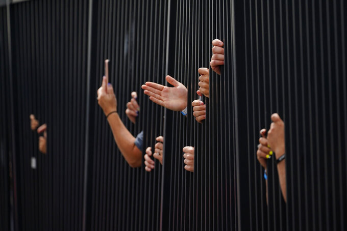 Fans stick their hands through a fence and take photos near the garages before a NASCAR Truck Series auto race at Pocono Raceway, Saturday, June 26, 2021, in Long Pond, Pa. (AP Photo/Matt Slocum)