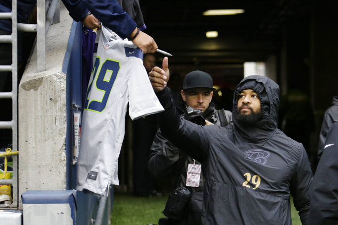 Baltimore Ravens free safety Earl Thomas reaches to sign a jersey bearing his number when he was with the Seattle Seahawks as he takes the field for warmups before an NFL football game against his former team, Sunday, Oct. 20, 2019, in Seattle. (AP Photo/John Froschauer)