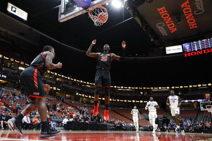 Cal State Northridge forward Lamine Diane celebrate a basket by guard Terrell Gomez, left, against UC Santa Barbara during the second half of a NCAA college basketball game at the Big West men's tournament in Anaheim, Calif., Thursday, March 14, 2019. (AP Photo/Chris Carlson)