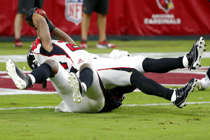 Atlanta Falcons running back Devonta Freeman, top, lunges for the end zone for a touchdown as Arizona Cardinals outside linebacker Haason Reddick defends during the second half of an NFL football game, Sunday, Oct. 13, 2019, in Glendale, Ariz. (AP Photo/Rick Scuteri)
