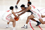 South Carolina guard AJ Lawson, center, dives for a loose ball between Houston guard Quentin Grimes (24) and forward Reggie Chaney (32) during the first half of an NCAA college basketball game Saturday, Dec. 5, 2020, in Houston. (AP Photo/Michael Wyke)